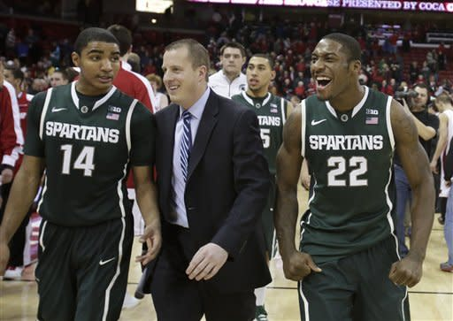 Michigan State's Gary Harris (14) assistant coach Dane Fife and Branden Dawson (22) walk off the court after Michigan State beat Wisconsin 49-47 in an NCAA college basketball game Tuesday, Jan. 22, 2013, in Madison, Wis. (AP Photo/Andy Manis)