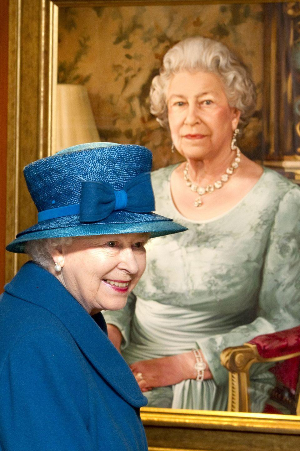 <p>QEII wore a blue jacket, matching hat, and pearl earrings as she looked at a commissioned portrait of herself in The Queen's Room at the Southampton docks.</p>
