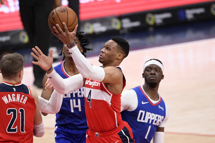 Washington Wizards guard Russell Westbrook (4) goes to the basket past Los Angeles Clippers guard Reggie Jackson (1) and guard Terance Mann (14) during the first half of an NBA basketball game, Thursday, March 4, 2021, in Washington. (AP Photo/Nick Wass)