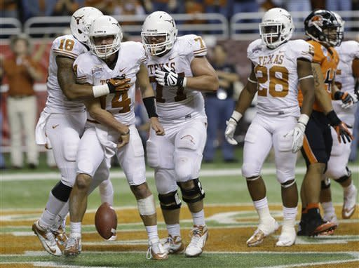 Texas' David Ash, second from left, celebrates with teammates after he scored during the third quarter of the Alamo Bowl NCAA football game against Oregon State, Saturday, Dec. 29, 2012, in San Antonio. Texas won 31-27. (AP Photo/Eric Gay)