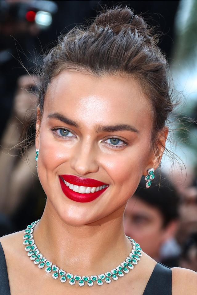 <p>Irina Shayk modelled the modern way to wear hot red lips; with barely-there eye make-up and a perfectly imperfect messy bun. </p>