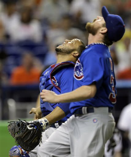 Chicago Cubs catcher Wellington Castillo, left, and pitcher Travis Wood chase a foul ball hit by Miami Marlins' Austin Kearns during the sixth inning of a baseball game in Miami, Saturday, April 27, 2013. Castillo caught the ball. (AP Photo/J Pat Carter)