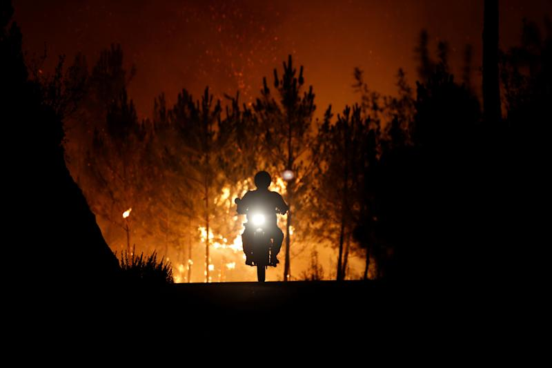 A firefighter rides a motorbike away from the fire around the village of Macao, near Castelo Branco, Portugal, on July 26, 2017.