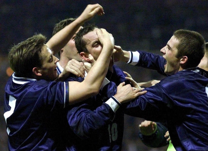 FILE - In this Wednesday, Nov. 17, 1999 file photo, Scotland's Don Hutchinson, center, is mobbed by teammates after scoring against England in their European Championship second leg, playoff soccer qualifier at London's Wembley stadium. The European Championship sees the 115th instalment of international soccer's oldest rivalry when England plays Scotland at Wembley Stadium on Friday June 18, 2021, 149 years after the first match between the two nations.(AP Photo/Max Nash, File)