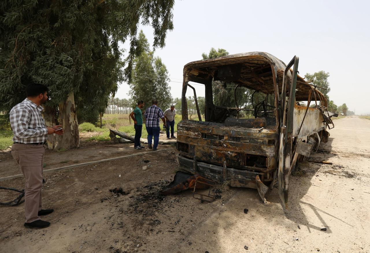 People look at a burnt bus in Taji, north of Baghdad July 24, 2014. A shooting and bombing attack on a bus near Baghdad killed 52 prisoners and nine policemen on Thursday, Ministry of Justice and medical sources said, the latest in a string of assaults on prisoners in Iraq. The motive for Thursday's killings was not immediately clear but Iraqi security forces and government affiliated Shi'ite militias appear to have unlawfully executed at least 255 prisoners over the past month in apparent revenge for killings by Sunni militants, according to Human Rights Watch. The bus was transporting prisoners from a military base in the town of Taji to Baghdad when it was hit by roadside bombs, the sources said. Gunmen then opened fire. REUTERS/Thaier al-Sudani (IRAQ - Tags: CIVIL UNREST POLITICS TRANSPORT)
