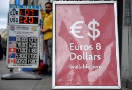 FILE PHOTO: Boards displaying buying and selling rates are seen outside of currency exchange outlets in London