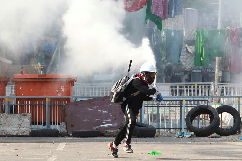 An anti-coup demonstrator sprays a fire extinguisher as he runs away from a barricade during a protests in Yangon