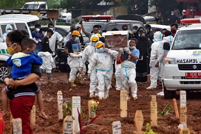 Funeral workers prepare to bury deceased Covid-19 coronavirus victims who were brought by ambulance directly from hospitals, at the Pedurenan public cemetery in Bekasi, West Java on 23 July 2021 (AFP via Getty Images)