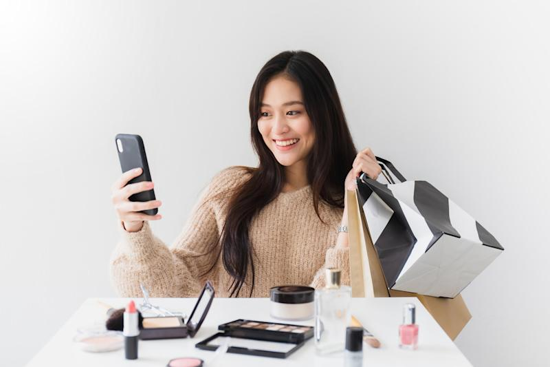 A young woman takes a selfie with purchased cosmetics products.