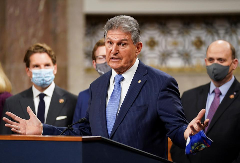U.S. Senator Joe Manchin (D-WVA) removes his mask to speak as bipartisan members of the Senate and House gather to announce a framework for fresh coronavirus disease (COVID-19) relief legislation at a news conference on Capitol Hill in Washington, U.S., December 1, 2020. REUTERS/Kevin Lamarque