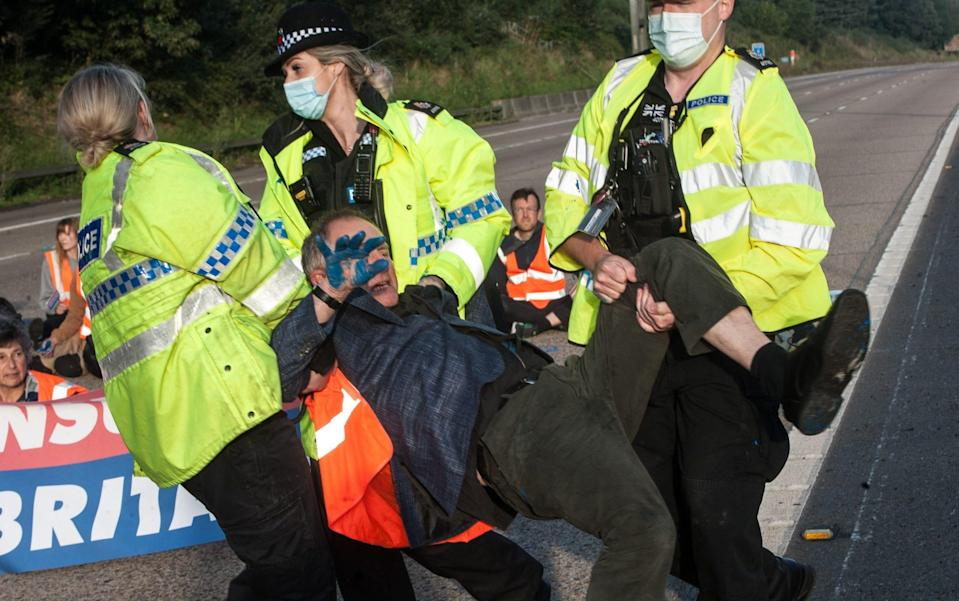 Police remove activists from the motorway as protestors from Insulate Britain block the M25 motorway - Guy Smallman/Getty Images