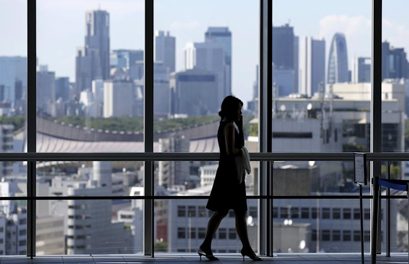 A woman uses her mobile phone at an office building in Tokyo July 21, 2015. Two in five Japanese firms plan to boost capital spending this business year, and more than a third of those say it is because of rising demand, a Reuters poll showed, pointing to a pickup in confidence about the economy. Picture taken July 21, 2015. REUTERS/Toru Hanai