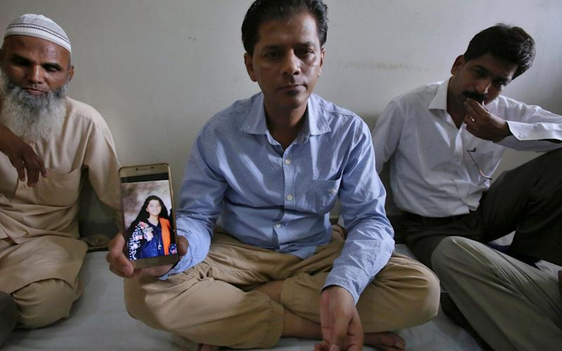 The father of Sabika Sheikh, a foreign exchange student shot dead in Texas, displays her photograph at his home in Karachi, Pakistan - AP