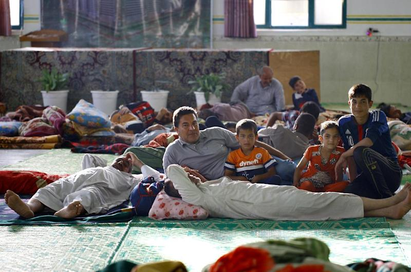 People rest at a shelter set-up for displaced Iraqis on June 29, 2014 in Najaf, Iiaq, as mainly Shiite Turkmen and some Christians, who fled from the northern city of Mosul are taking refuge (AFP Photo/Haidar Hamdani )