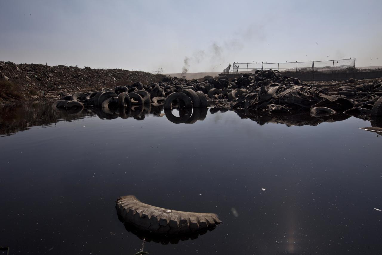A damaged tires sit in a puddle at the landfill Bordo Poniente on the outskirts of Mexico city, Monday, Dec. 19, 2011. Mexico City will close one of the world's largest dumps by Dec. 31 and will instead turn the garbage from millions of people into reusable materials and energy, Mayor Marcelo Ebrard announced Monday. (AP Photo/Christian Palma)
