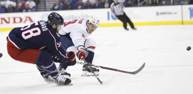 Columbus Blue Jackets' David Savard, left, knocks the puck away from Washington Capitals' Dmitry Orlov, of Russia, during the first period of Game 6 of an NHL first-round hockey playoff series Monday, April 23, 2018, in Columbus, Ohio. (AP Photo/Jay LaPrete)