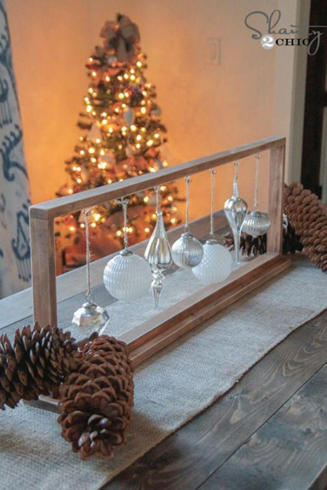 """<p>Christmas bulbs don't just belong on the tree: highlight some of your favorites on the dinner table with this elegant frame. </p><p><strong>Get the tutorial at <a href=""""http://www.shanty-2-chic.com/2014/12/diy-christmas-centerpiece.html"""" rel=""""nofollow noopener"""" target=""""_blank"""" data-ylk=""""slk:Shanty 2 Chic"""" class=""""link rapid-noclick-resp"""">Shanty 2 Chic</a></strong><strong>.</strong></p><p><strong><a class=""""link rapid-noclick-resp"""" href=""""https://www.amazon.com/KI-Store-Shatterproof-Decorations-Decoration/dp/B016NQ63PA/?tag=syn-yahoo-20&ascsubtag=%5Bartid%7C10050.g.644%5Bsrc%7Cyahoo-us"""" rel=""""nofollow noopener"""" target=""""_blank"""" data-ylk=""""slk:SHOP ORNAMENTS"""">SHOP ORNAMENTS</a></strong></p>"""