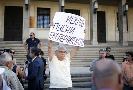 Depositor at Bulgaria's Corporate Commercial Bank holds a sign during a demonstration demanding access to their accounts in Corpbank, in front of the Bulgarian National Bank in Sofia