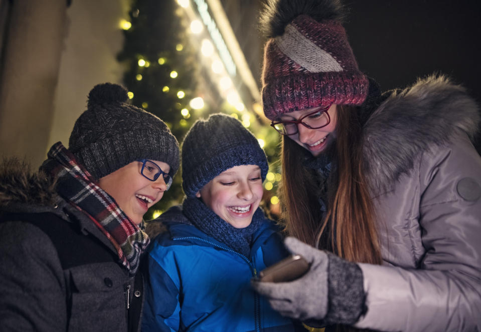 Brother and sister having fun outdoors near Christmas market. City Christmas decorations visible in the background.  Kids are checking the shopping list on the smartphone. Nikon D850