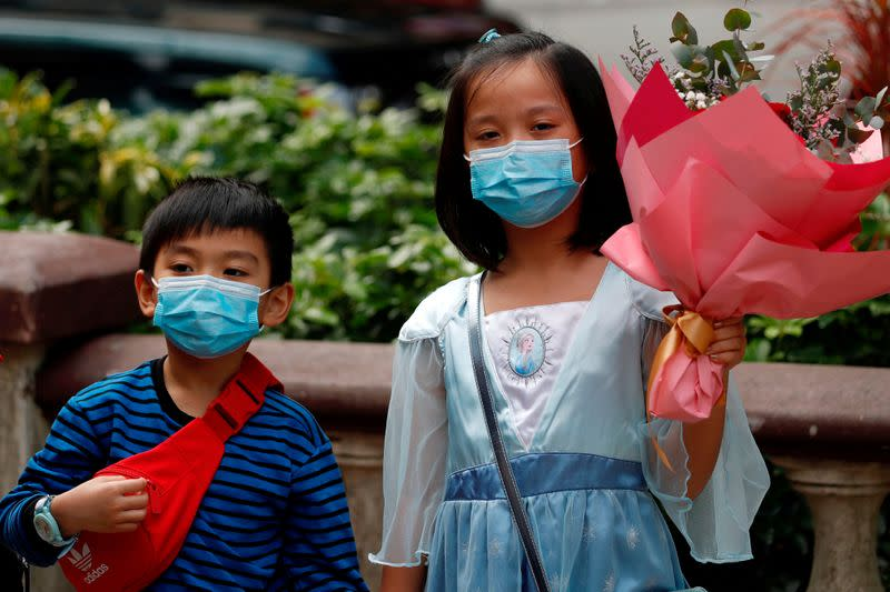 FILE PHOTO: Children wear face masks, following the outbreak of the novel coronavirus on Valentine's Day in Hong Kong