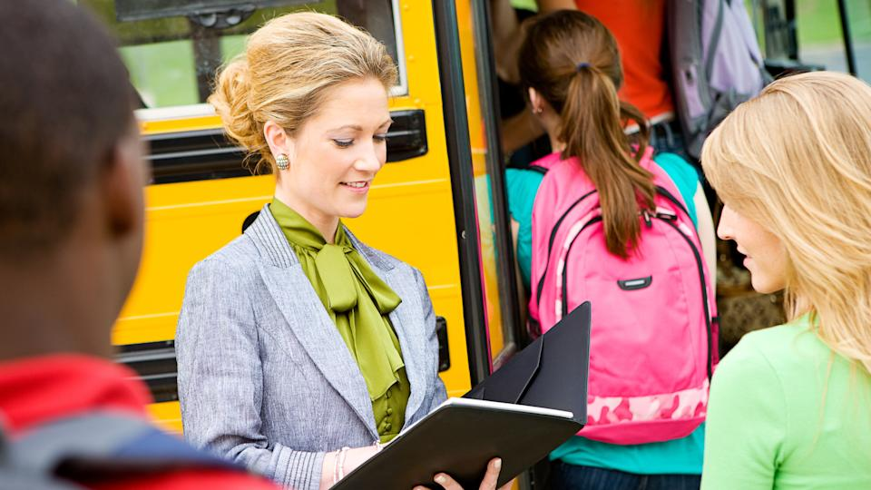 school administrator with kids at bus stop