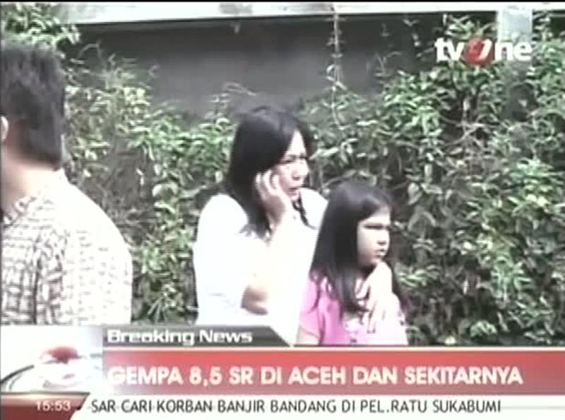 In this image made from Indonesian television TV One, a woman hugging a girl uses a mobile phone shortly after they ran out from a building when a strong earthquake hit in Aceh in Indonesia, Wednesday, April 11, 2012. A tsunami watch was issued for countries across the Indian Ocean after a large earthquake hit waters off Indonesia on Wednesday, triggering widespread panic as residents along coastlines fled to high ground in cars and on the backs of motorcycles. (AP Photo/TV One via AP Video) INDONESIA OUT