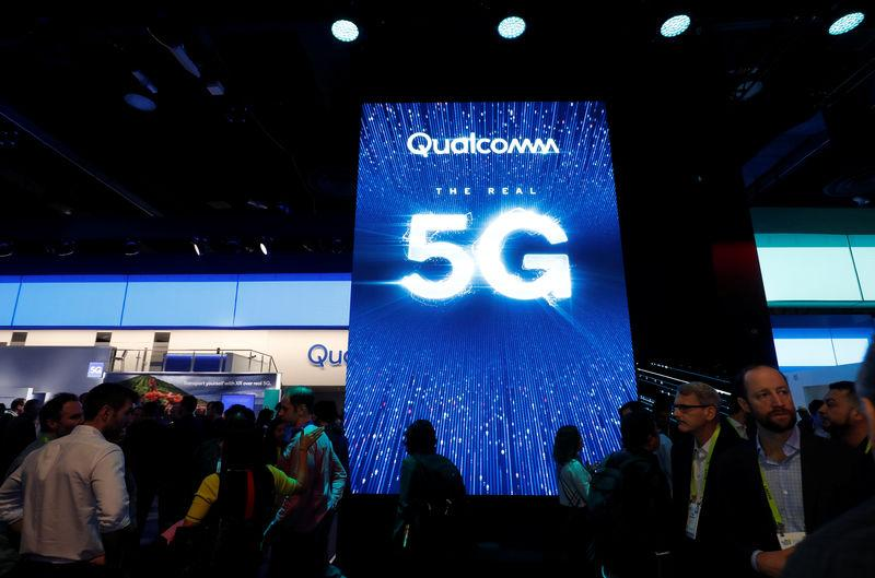People walk by a video display promoting 5G connectivity at the Qualcomm booth during the 2019 CES in Las Vegas