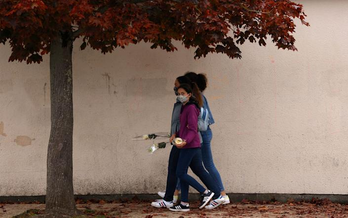 Teenagers arrive to lay flowers in front of Bois d'Aulne middle school