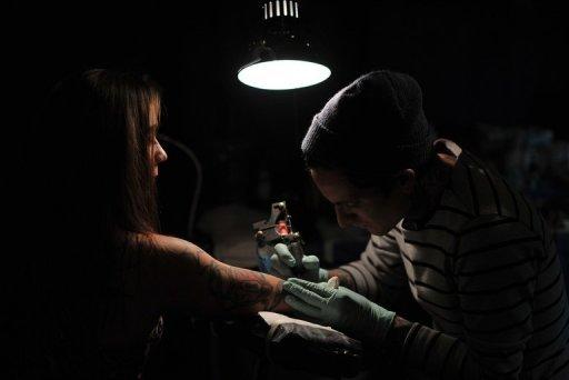 A woman gets a tattoo during the New York City Tattoo Convention on May 19. US women took over men for the first time this year in terms of numbers of tattoos, with 23% of females bearing a tattoo, compared to 19% of men, according to a Harris poll