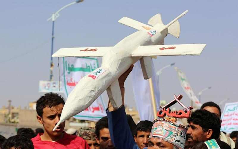 Followers of the Houthi movement carry a mock drone during a rally on September 10 - REUTERS