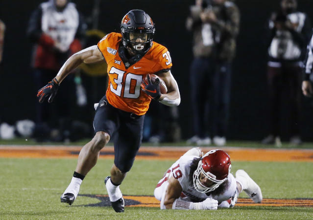 FILE - In this Nov. 30, 2019, file photo, Oklahoma State running back Chuba Hubbard (30) carries past Oklahoma linebacker Caleb Kelly during an NCAA college football game in Stillwater, Okla. Hubbard said on Twitter that he wont do anything with the program until there is change after coach Mike Gundy was photographed wearing a T-shirt representing far-right online publication One America News Network. Gundy is seen in a photograph on Twitter wearing the T-shirt with the letters OAN. (AP Photo/Sue Ogrocki, File)
