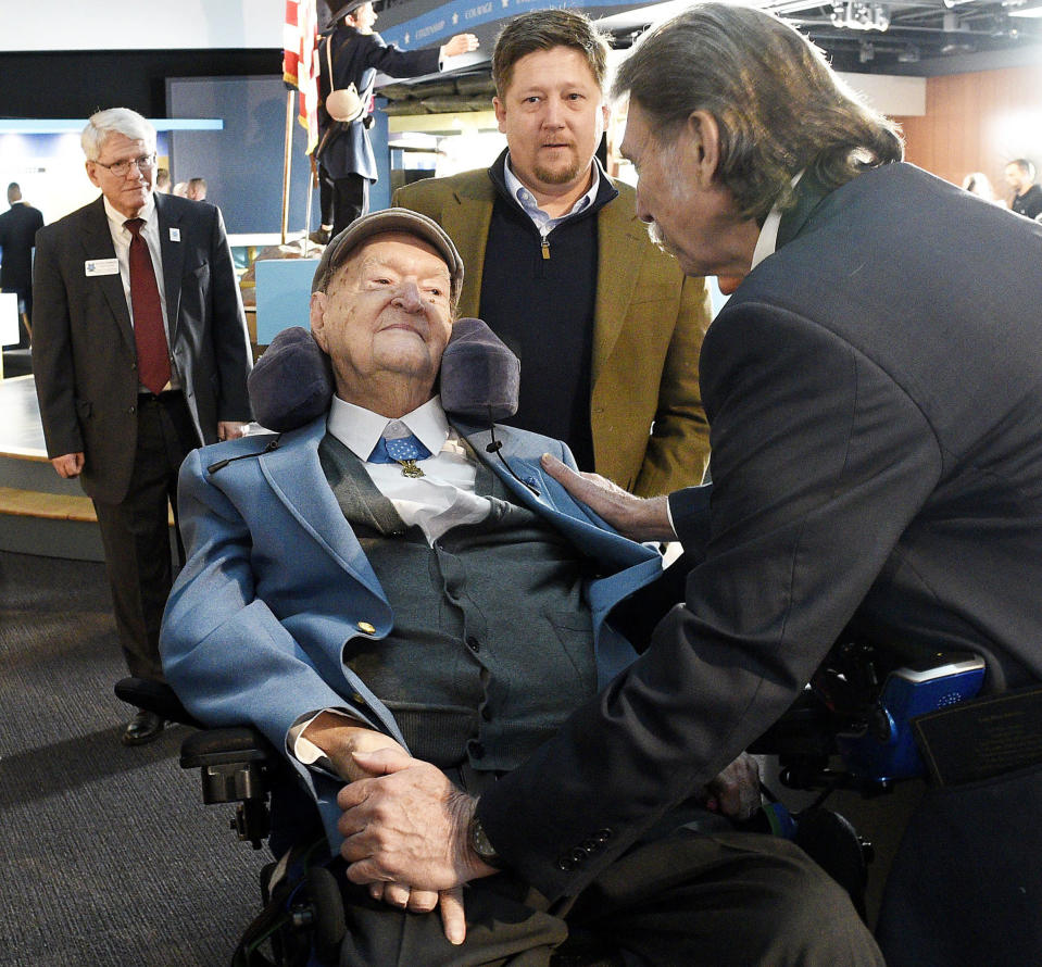 Charles Coolidge is greeted by Desmond Doss Jr., right, while Center Executive Director Keith Hardison and Mr. Coolidge's grandson, J.C. Coolidge look on, during a dedication ceremony at The Charles H. Coolidge National of Medal of Honor Heritage Center on Saturday, February 22, 2020., in Chattanooga, Tenn. Tennessee Metal of Honor recipient Charles H. Coolidge has died at age 99. The Congressional Medal of Honor Society announced in a statement that Coolidge died Tuesday, April 6, 2021, in Chattanooga. (Robin Rudd/Chattanooga Times Free Press via AP)