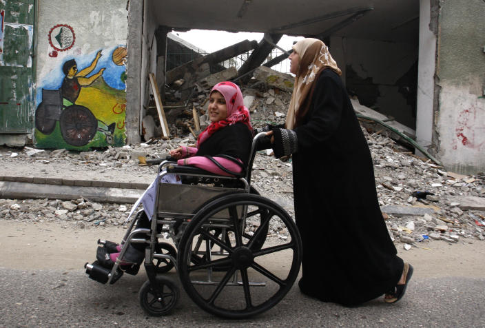 """A Palestinian woman pushes a girl in a wheelchair past a destroyed stadium during a march to mark the UN International Day of People with Disability in Gaza City, Tuesday, Dec. 4, 2012. Each year the day focuses on a different issue and the theme this year is """"Removing barriers to create an inclusive and accessible society for all."""" (AP Photo/Hatem Moussa)"""