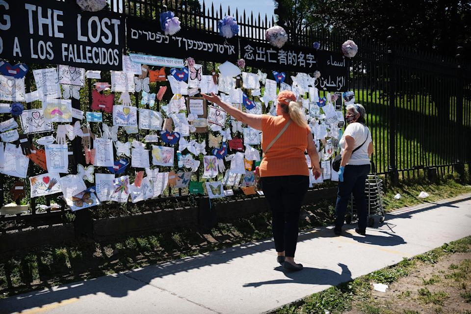 People walk by a memorial for those who have died from the coronavirus outside Green-Wood Cemetery on May 27, 2020, in the Brooklyn borough of New York City. Green-Wood Cemetery, one of New York's oldest cemeteries, has been the site of hundreds of burials and cremations of COVID-19 victims.