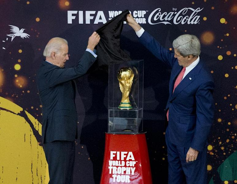 Vice President Joe Biden, left, and Secretary of State John Kerry, unveil the FIFA World Cup trophy, the actual trophy that will be awarded to the winner of this year's World Cup soccer tournament in Brazil, Monday, April 14, 2014, during a ceremony at the State Department in Washington. (AP Photo/Manuel Balce Ceneta)