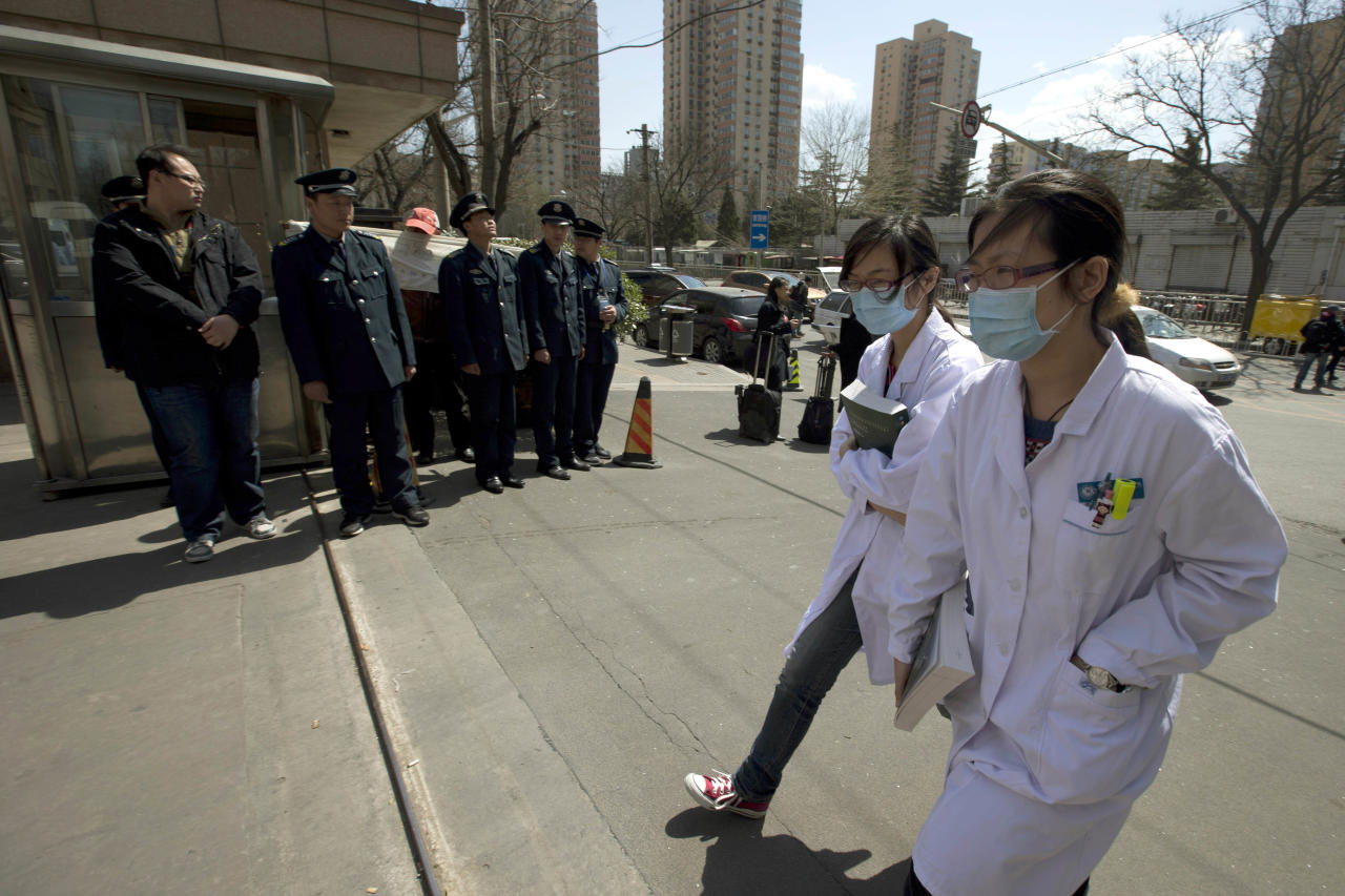 Chinese health workers, wearing masks, walk past a group of security guards blocking a petitioner outside China's Health Ministry where a joint press conference between Chinese health officials and World Health Organization representatives was held in Beijing, China, Monday, April 8, 2013. The World Health Organization is talking with the Chinese government about sending international experts to China to help investigate a new bird flu strain that has killed six. Most of the 21 people stricken so far got severely ill. (AP Photo/Ng Han Guan)