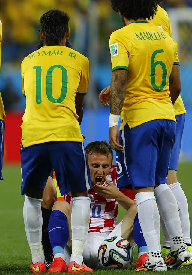 Brazil's Neymar (L) helps Croatia's Luka Modric (C) after Neymar was shown the yellow card during their 2014 World Cup opening match at the Corinthians arena in Sao Paulo June 12, 2014. REUTERS/Ivan Alvarado (BRAZIL - Tags: SOCCER SPORT WORLD CUP)