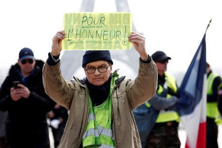 """A protester holds a placard reading """"For the Honour"""" in front of the Eiffel Tower during the Act XIX, the 19th round of Saturday protests by the """"yellow vests"""" movement, in Paris, France, March 23, 2019. REUTERS/Benoit Tessier"""