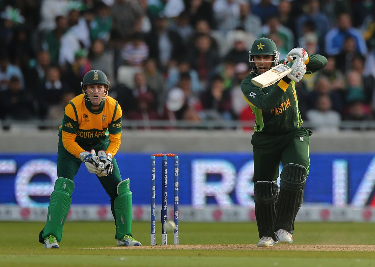 Pakistan batsman Misbah ul Haq drives a shot watched South Africa wicketkeeper AB de Villers during the ICC Champions Trophy match at Edgbaston, Birmingham.