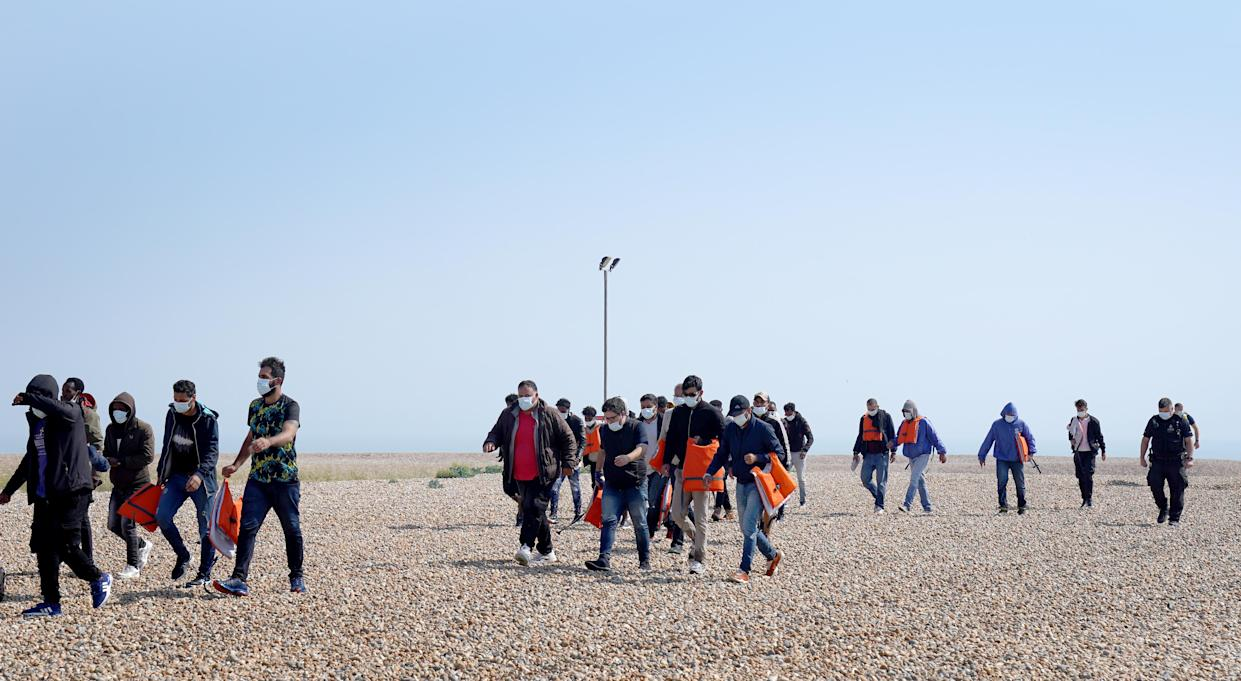 A group of people thought to be migrants are escorted from the beach in Dungeness, Kent, by Border Force officers following a small boat incident in the Channel. Picture date: Tuesday July 20, 2021.