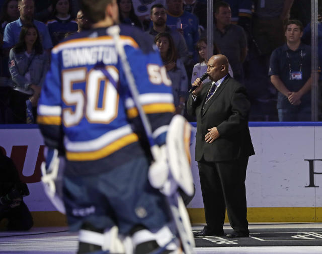 Charles Glenn sings the national anthem as St. Louis Blues goaltender Jordan Binnington (50) listens before the start of Game 6 of the NHL hockey Stanley Cup Final between the Blues and the Boston Bruins Sunday, June 9, 2019, in St. Louis. (AP Photo/Jeff Roberson)