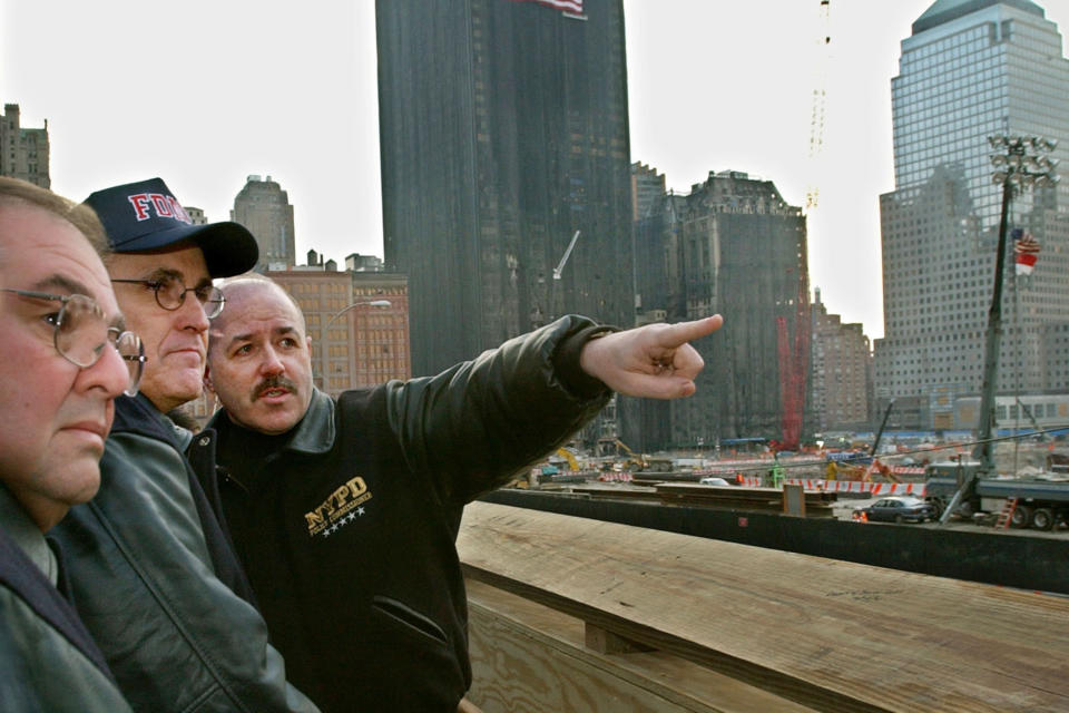 FILE - In this Dec. 29, 2001 file photo, New York Mayor Rudy Giuliani, center, is flanked by New York Police Commissioner Bernard Kerik, right, and the Mayor's Office of Emergency Management Director Richard Scheirer, before dedicating a public viewing platform overlooking the site of the World Trade Center attacks in New York. (AP Photo/Kathy Willens, File)