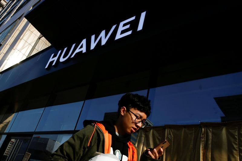 FILE PHOTO: A man uses his phone as he walks past a Huawei shop in Beijing