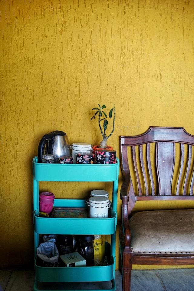 Pops of mustard yellow and teal highlight spaces within the home as seen in this signature wall and floating chai bar (a trolley by Ikea).