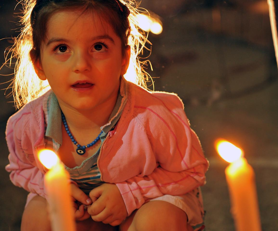A Kosovo child sits by candles lit by citizens to mark the 10th anniversary of the 9/11 terror attacks on the United States, in capital Pristina, Kosovo, on Sunday, Sept. 11, 2011. ( AP Photo / Visar Kryeziu )
