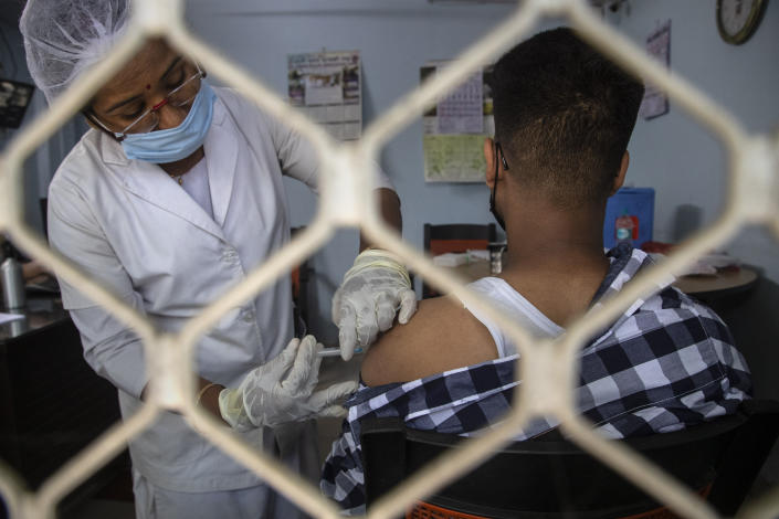 A health worker administers the Covishield vaccine for COVID-19 to a journalist at the press club in Gauhati, India, Friday, Aug. 6, 2021. (AP Photo/Anupam Nath)