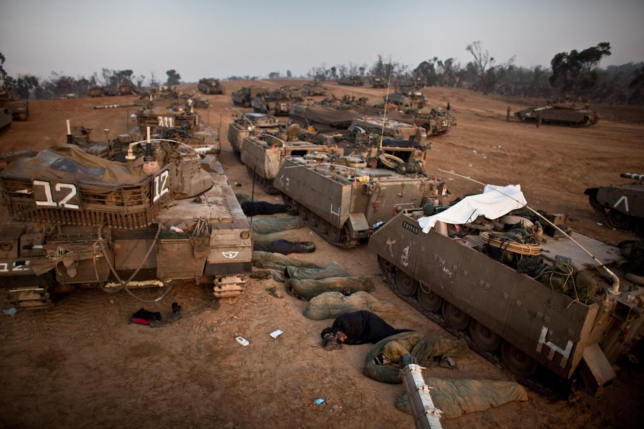 ISRAEL/GAZA BORDER, ISRAEL- NOVEMBER 19:  (ISRAEL OUT) Israeli soldiers sleep next to their tanks in a deployment area on November 19, 2012 on Israel's border with the Gaza Strip. The death toll has risen to at least 85 killed in the air strikes, according to hospital officials, on day six since the launch of operation 'Pillar of Defence.'  (Photo by Uriel Sinai/Getty Images)