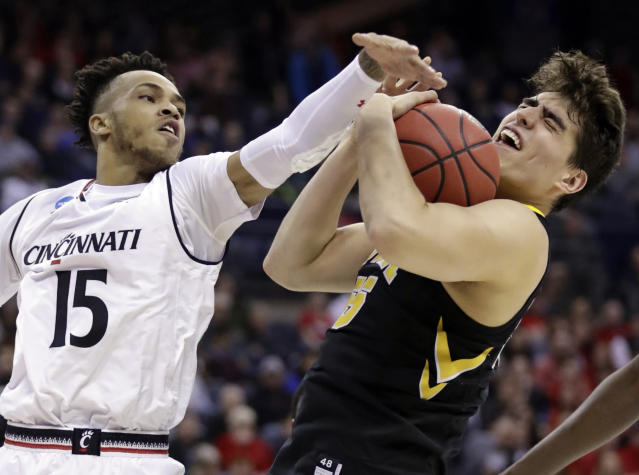 <p>Iowa's Luka Garza (55) grabs a rebound ahead of Cincinnati's Cane Broome (15) in the first half during a first round men's college basketball game in the NCAA Tournament in Columbus, Ohio, Friday, March 22, 2019. (AP Photo/Tony Dejak) </p>