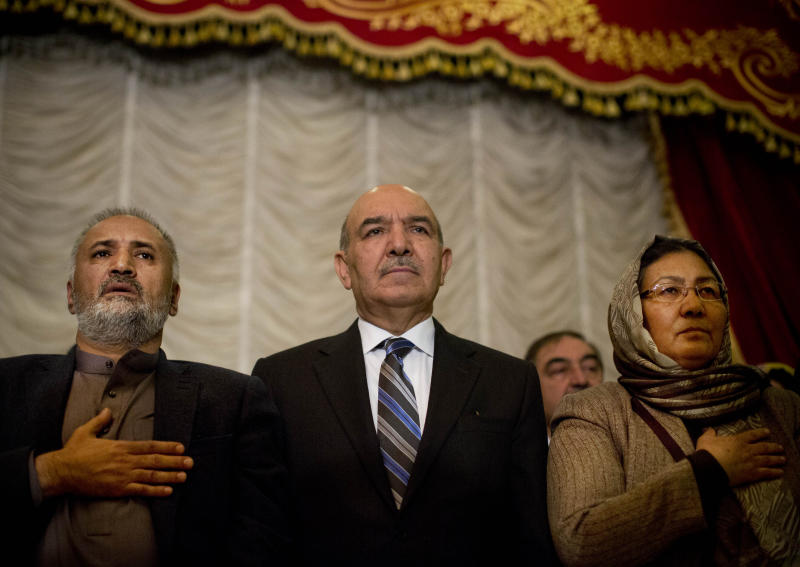 Former Afghanistan's presidential candidate Qayyum Karzai, center, stands up for the national anthem during a meeting with supporters of presidential candidate and former foreign minister Zalmai Rassoul in Kabul, Afghanistan, Wednesday, March 26, 2014. Qayyum Karzai, brother of Afghan President Hamid Karzai, withdrew form the presidential race earlier and threw his support behind front runner Zalmai Rassoul. (AP Photo/Anja Niedringhaus)