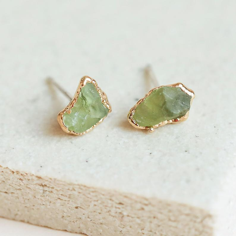 """<h2>August: Peridot<br></h2> <br><strong>The Signs: Leo & Virgo<br></strong><br>According to Oldershaw, brilliant-green peridot gets its name from the French <em>peritot</em>, which means """"gold"""". Its verdant hue, however, is due to trace amounts of iron in the stone. A gem that possesses the beauty of gold and the strength of iron sounds like the perfect fit for a dependable Virgo or a fiercely loyal Leo.<br><br><br><strong>DANIBARBEshop</strong> Gold Plate Natural Peridot Studs, $, available at <a href=""""https://go.skimresources.com/?id=30283X879131&url=https%3A%2F%2Fwww.etsy.com%2Flisting%2F573985967%2Faugust-birthstone-studs-raw-crystal"""" rel=""""nofollow noopener"""" target=""""_blank"""" data-ylk=""""slk:Etsy"""" class=""""link rapid-noclick-resp"""">Etsy</a>"""